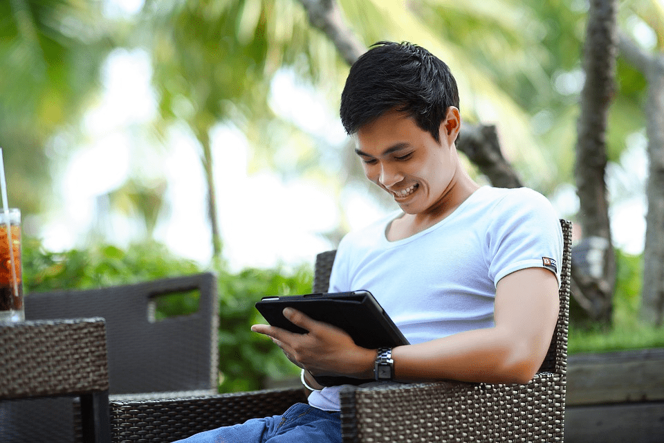 A person reading content on a tablet and smiling